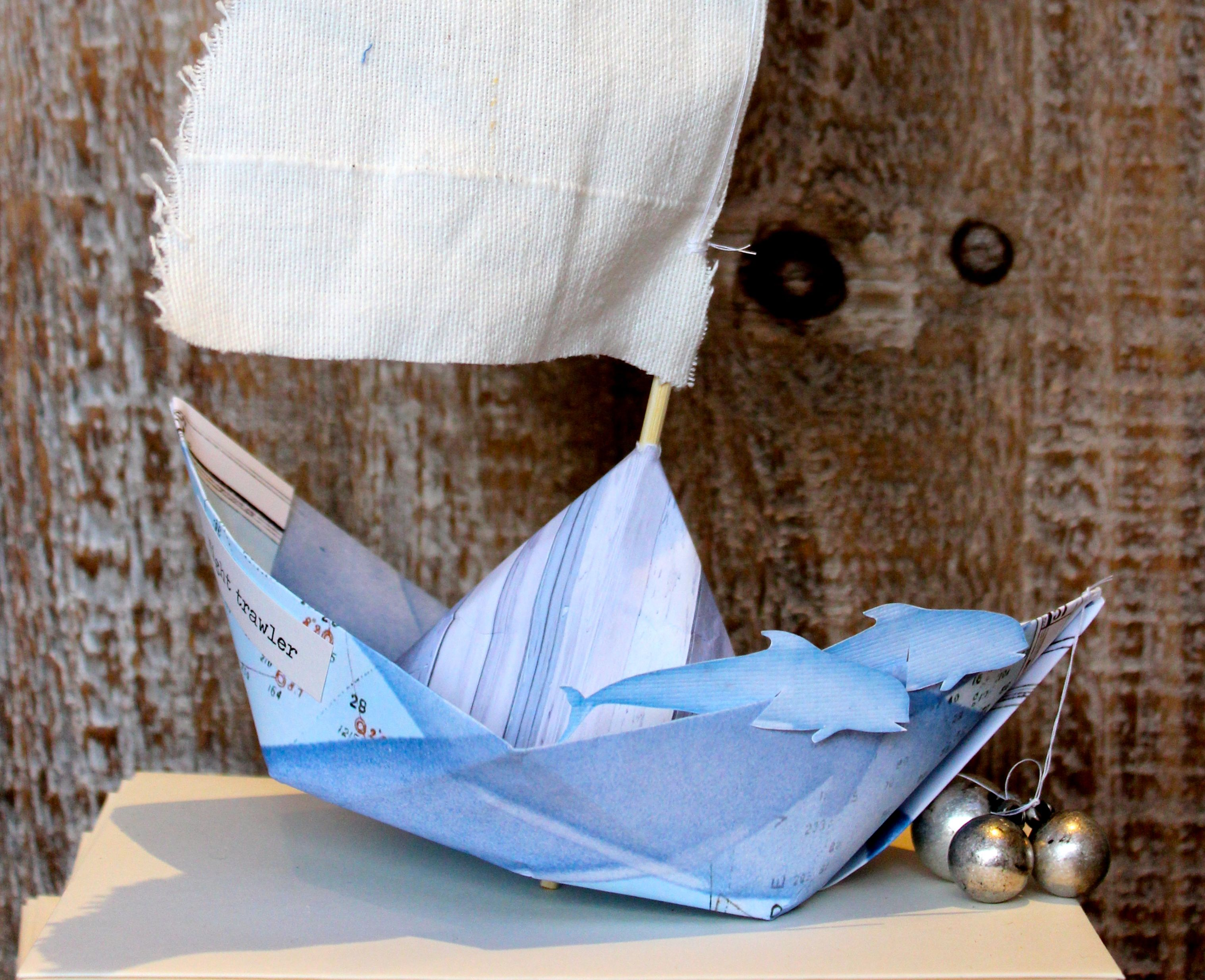 paper boat with anchor and paper dolphins, and linen sail