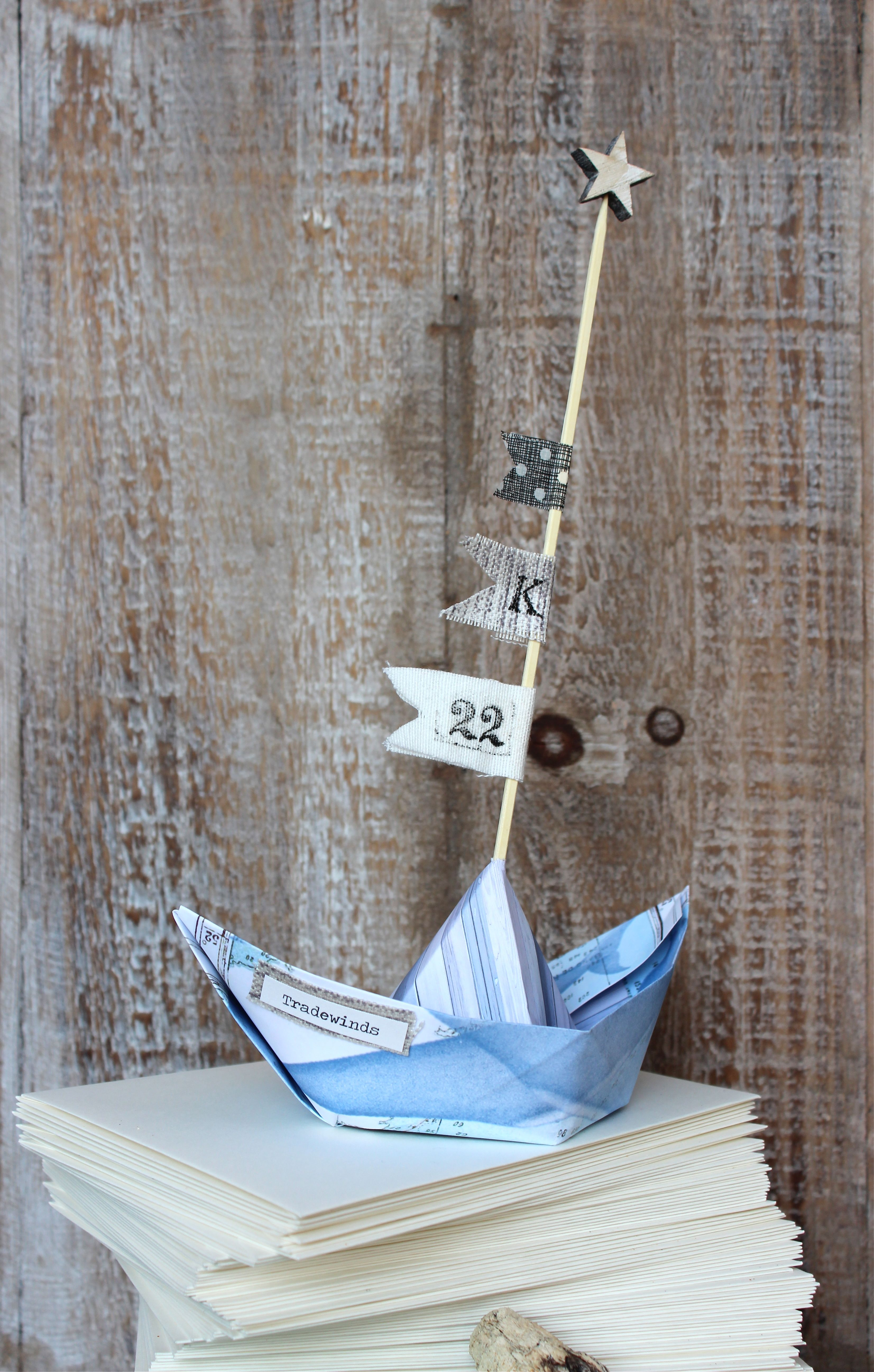 tradewinds paper boat with mast and ribbon flags
