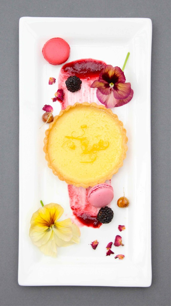 Lemon tart with edible nasturtium flowers and macarons